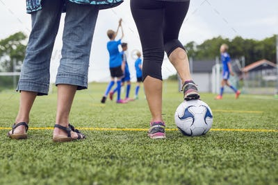 Low section of women in soccer field, boys (10-11, 12-13, 14-15) playing in background