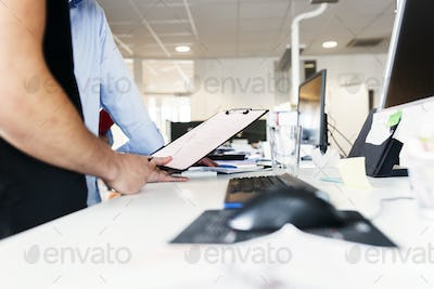 Colleagues standing with clipboard in office
