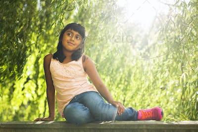 Portrait of girl (6-7) sitting in park