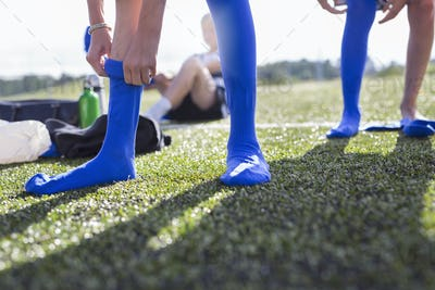 Low section of boys (10-11) putting on soccer socks