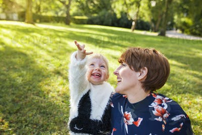 Mother laughing with daughter (2-3) in park