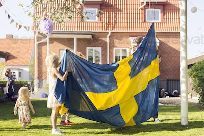 Dad with daughters (18-23 months, 8-9) holding Swedish flag