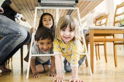 Children (2-3, 6-7) hiding under table, adults sitting at table