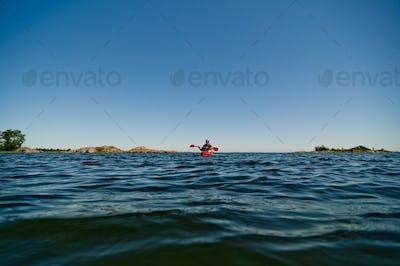 Man paddling in sea at sunset