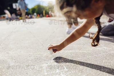 Girl (6-7) drawing on asphalt