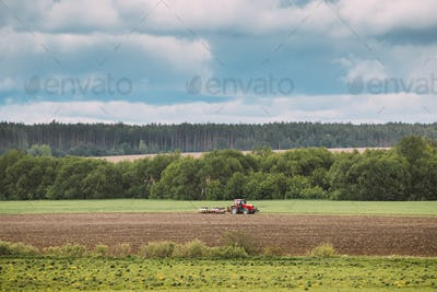Tractor Plowing Field In Spring Season. Beginning Of Agricultural Spring Season. Cultivator Pulled