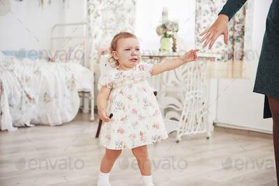 Childhood concept. sad and depressed little girl cries in Kindergarten. White vintage childroom