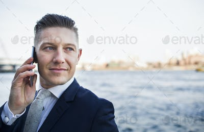 Close-up of businessman using smart phone while standing against river