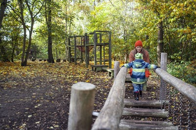 Boy walking towards mother during obstacle course in forest