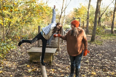 Mother helping daughter to walk on wooden beam in forest