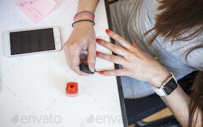 Midsection of businesswoman applying nail polish while sitting at desk in office