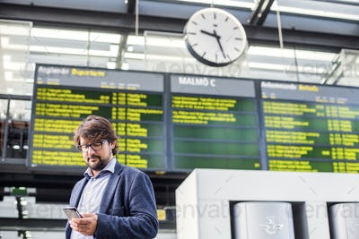 Low angle view of businessman using smart phone at railroad station
