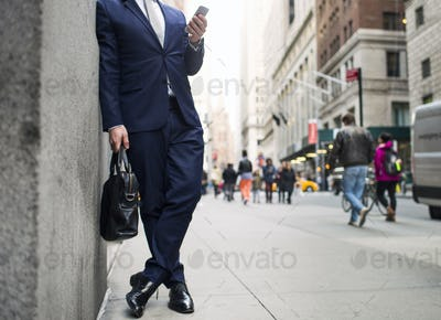 Low section of businessman holding bag and using smart phone while standing on sidewalk