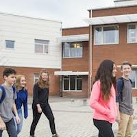 Children (12-13) in front of school building