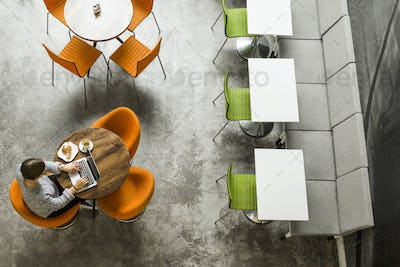High angle view of woman using laptop while having breakfast at coffee shop