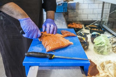 Midsection of fish vendor cutting salmon on cutting board at supermarket