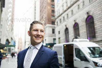 Confident smiling businessman standing on sidewalk against car in city