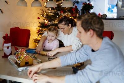 Family preparing gingerbread cookies at home