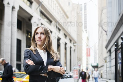 Close-up of confident businesswoman with arms crossed standing against building