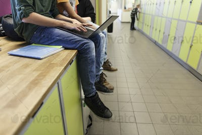 Boys (12-13) using laptop and sitting on lockers in school corridor