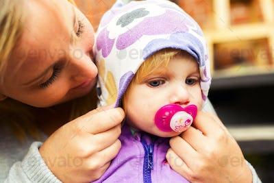 Mother adjusting hood on baby's head