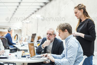 Concentrated business people preparing project on laptop in office