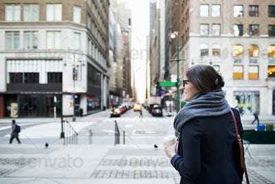 Businesswoman holding disposable cup while waiting by road in city