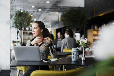 Confident businesswoman with laptop drinking coffee at table in restaurant