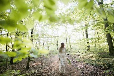 Beautiful bride walking in forest