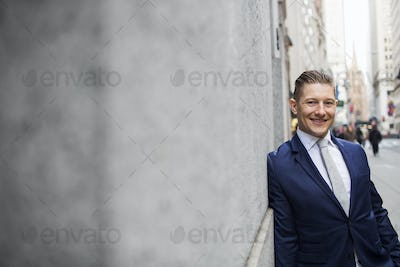 Portrait of smiling businessman leaning on wall