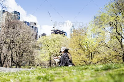 Woman sitting on grass against trees and buildings at Central Park