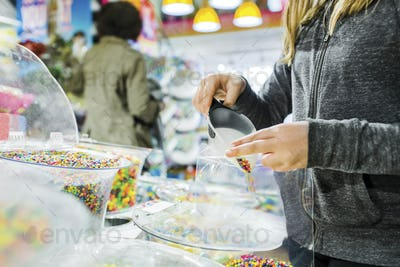 Midsection of girl filling candies in plastic while buying at shop