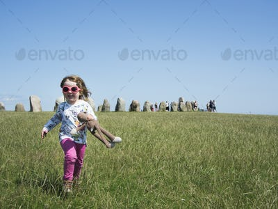 Girl holding stuffed toy while running on grassy field