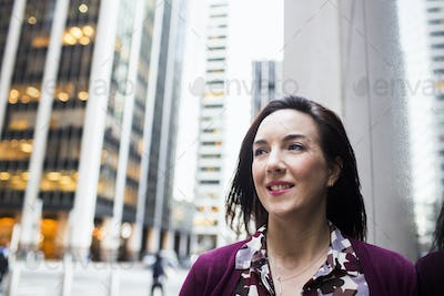 Close-up of confident businesswoman standing against buildings in city