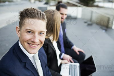 Portrait of smiling businessman sitting with colleagues using laptop