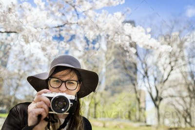 Close-up of young woman with camera standing against trees at Central Park