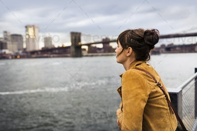 Side view of woman looking at East River while standing against Brooklyn bridge