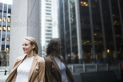 Close-up of confident businesswoman standing by glass window against buildings in city
