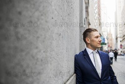 Confident businessman leaning against wall on sidewalk in city