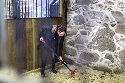 Full length of woman cleaning dung in stable