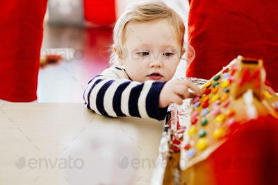 Girl decorating gingerbread house at table during Christmas