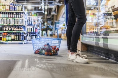 Low section of young man standing by shopping basket in supermarket