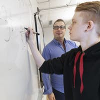 Schoolboy (12-13) writing on whiteboard, teacher watching