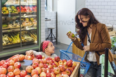 Happy mother and daughter shopping fruits in supermarket