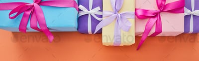 Flat Lay With Multicolored Gift Boxes With Ribbons And Bows on Orange Background With Copy Space