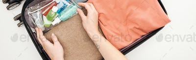 Panoramic Shot of Woman Packing Travel Bag on White Background