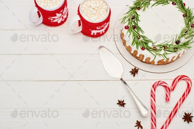 Christmas Pie, Candy Canes And Two Cups of Cocoa With Marshmallows on White Wooden Table