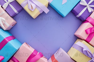 Top View of Colorful Presents With Bows on Purple Background With Copy Space