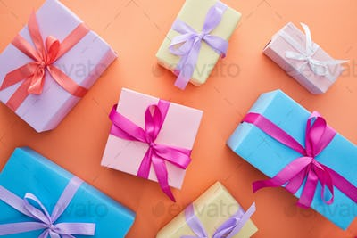 Top View of Multicolored Gift Boxes With Ribbons And Bows on Orange Background