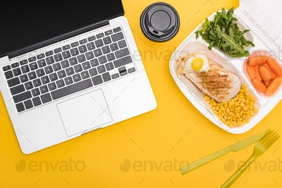 Paper Cup, Laptop And Eco Package With Vegetables, Meat, Fried Egg And Arugula Isolated on Yellow